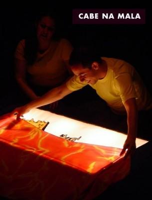 Mala, avental, caixas de pano que viram tapetes e caixa de luz servem de cenário para histórias de Ana Maria Machado e Jutta Bauer. As crianças se sentam próximas aos contadores para acompanhar a trajetória dos bonecos de pano em seus cenários de sonho, luz e textura.   Duração: 50 minutos. Para crianças a partir de 3 anos.